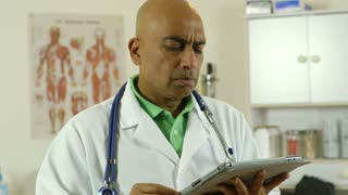 doctor looking at notes on his tablet pc