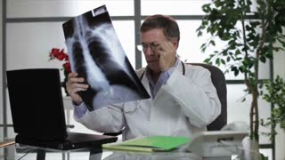 Doctor studing Xray and typing