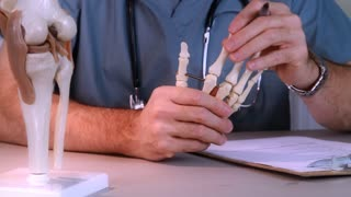 doctor studying a hand joint
