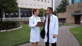 doctors talking walks past camera