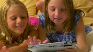 dolly left little girls playing with a tablet pc.