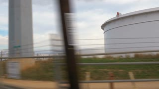 driving past an oil industrial complex over railroad tracks 4k