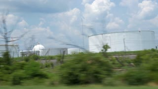 driving view of large petrochemical storage tanks