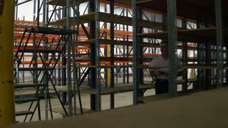 Engineer with smartphone walks through empty industrial warehouse shelves