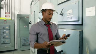 engineer with tablet and cell in electrical room.