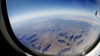 fisheye view of a mountain range out of a passenger jet window 4k