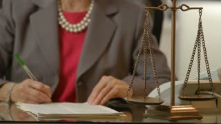 focus on scales of justice while woman lawyer signs legal papers