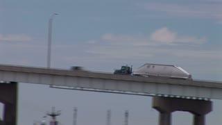 Follow shot of a truck traveling over a bridge