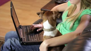 girl with her dog on couch smile at camera