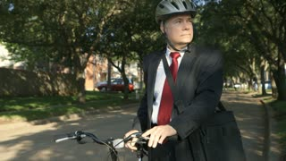 green concept businessman on bike smiles at camera.