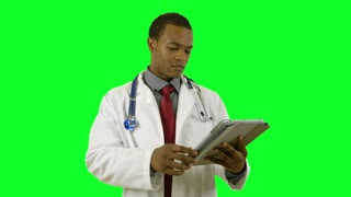 Green screen doctor looking at tablet pc