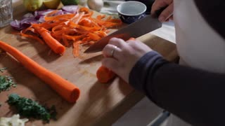 hand held of chef cutting carrots