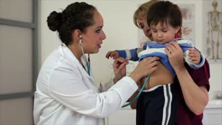 Hispanic doctor checking a little boy's breathing