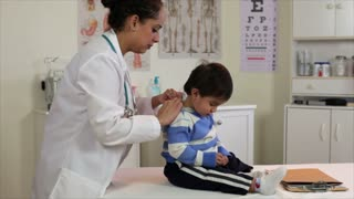 Hispanic doctor checking a small boy