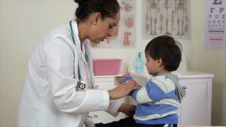 Hispanic doctor going over a little boy.