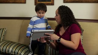 Hispanic mom showing her son something on a tablet.