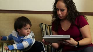 Hispanic mom with electronic tablet shows toddler.