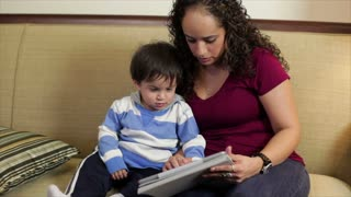 Hispanic mom with toddler using an electronic tablet