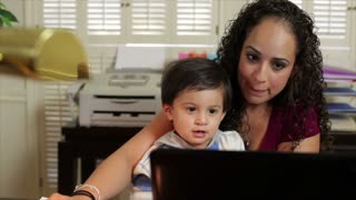 Hispanic mom working with baby