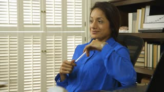hispanic woman ceo thinking and smiles at camera