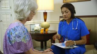 An experienced Hispanic home health nurse going over with an elderly patient how to manage her daily medications.
