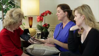 Home healthcare nurse taking blood pressure