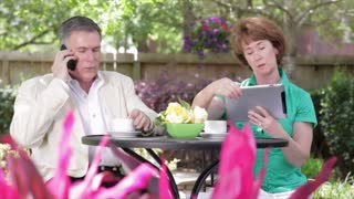 Husband and wife on the phone and tablet