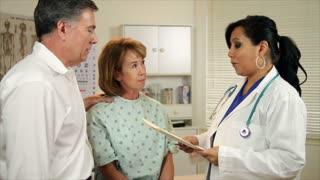 husband and wife talk to Hispanic woman doctor