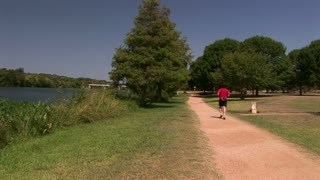 joggers on an open path next to a lake