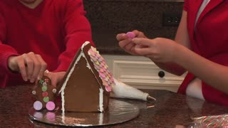 kids making the gingerbread house
