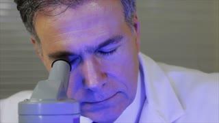 lab tech looks in microscope wide