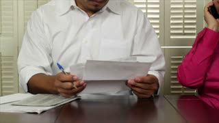 Latino man going over bills and want ads in newspaper
