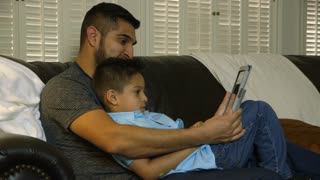 little boy and his dad looking at a tablet pc