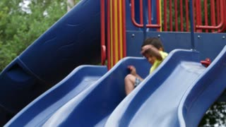 little boy playing on a slide and runs off.