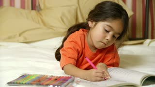 little girl coloring in bed