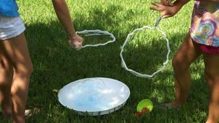 little girls making bubbles outside