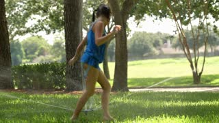 little girls playing in the lawn sprinkler.