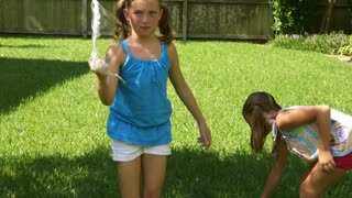 little girls playing with bubbles in the yard.
