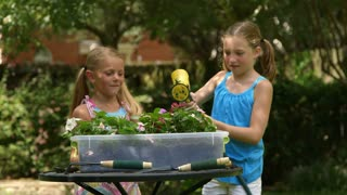 little girls watering the plants and play.