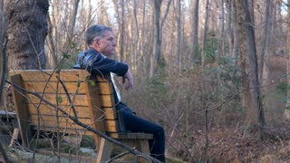 lonely man sitting on a bench in a park lost in his thoughts