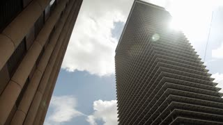 looking up at some highrise office buildings with sun flare 4k