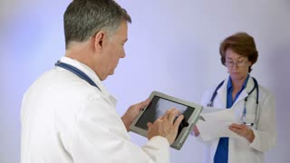 male doctor looking at an xray on a tablet pc other doctor in background