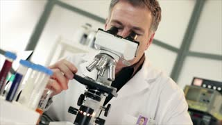 male scientist looking into a microscope