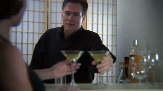 man and woman toasting martinis