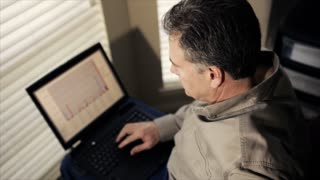 man at window with laptop smiles