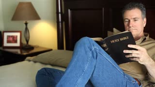 man bed reading bible