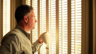 man drinking coffee at window