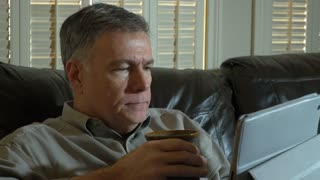 man drinking coffee while using a tablet pc