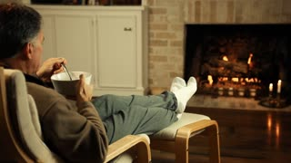 man eating cereral in front of fireplace