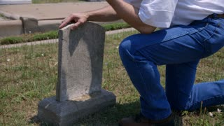man grieving at a grave site